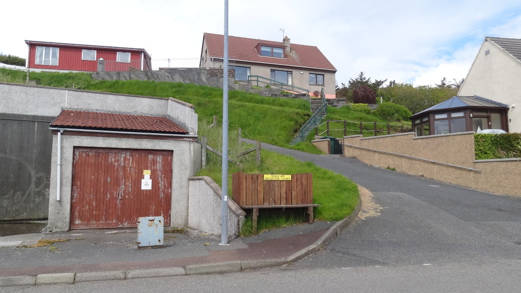 houses on a uphill street with a bench on the street corner
