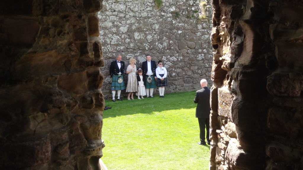Family dressed in kilt posing for a wedding photographer