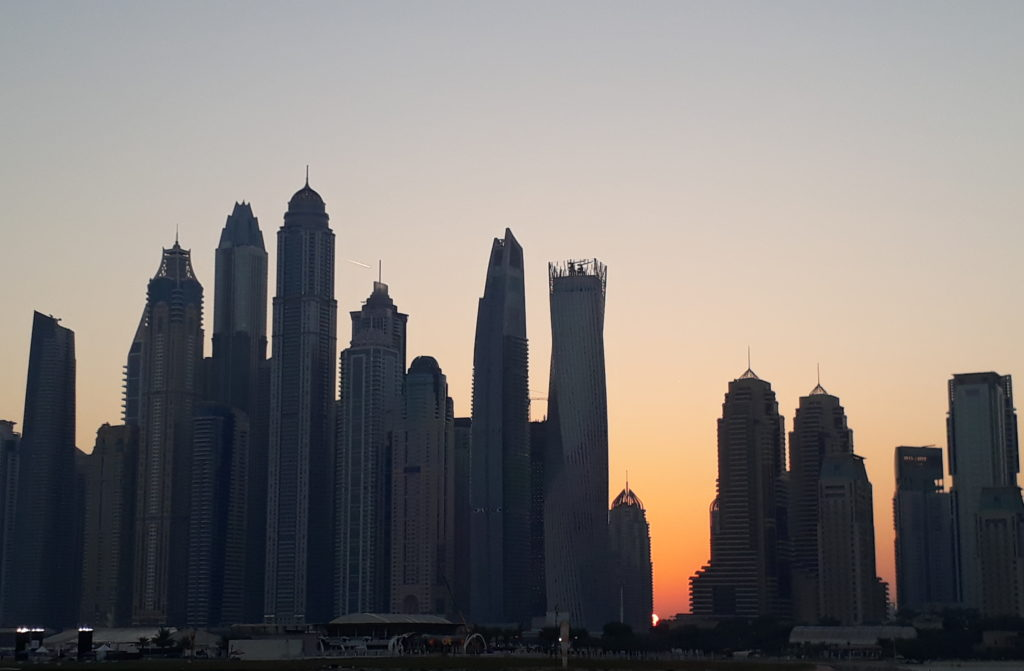 Sunrise behind dubai marina tower buildings