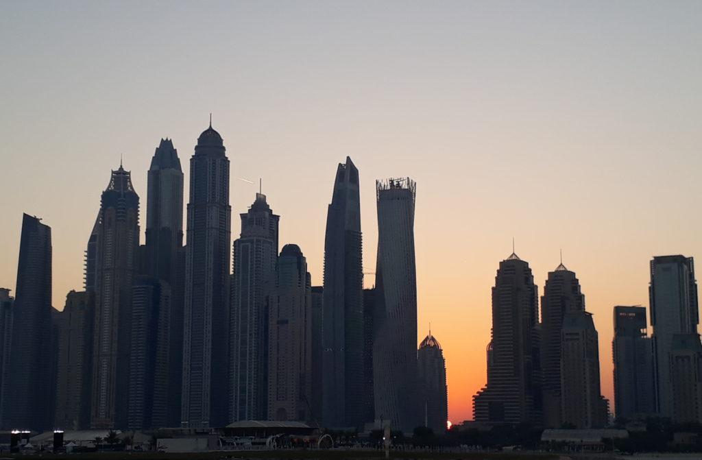 Sunrise behind dubai marina tower buildings