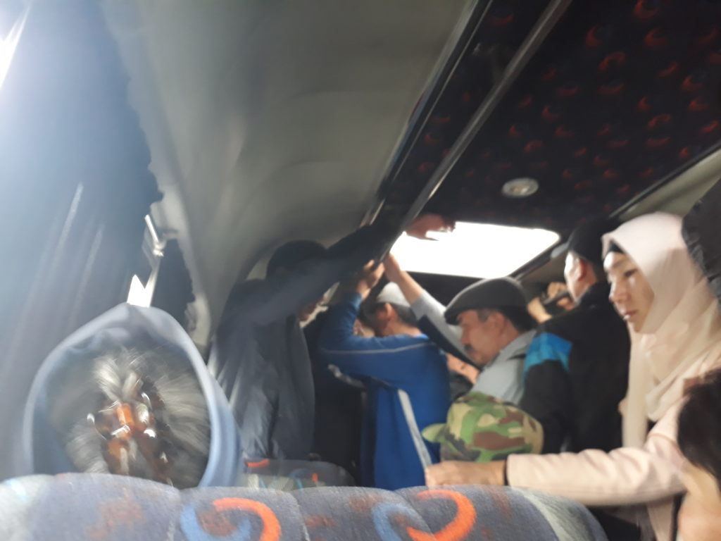 People standing in a packed minibus